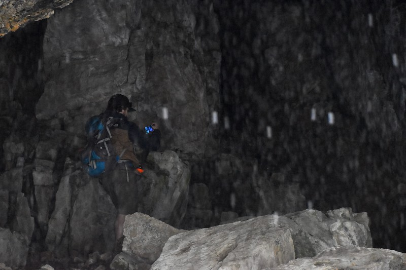 Hiker inside of the brown bat cave.  <br /> <br /> The white streaks are water droplets.