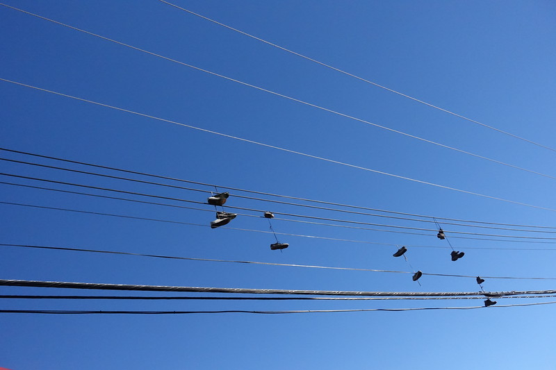 "As we are touring the alleys of Banff, I am informed that clusters sneakers hanging from power lines such as these indicates a ""crack house"" in the vicinity."
