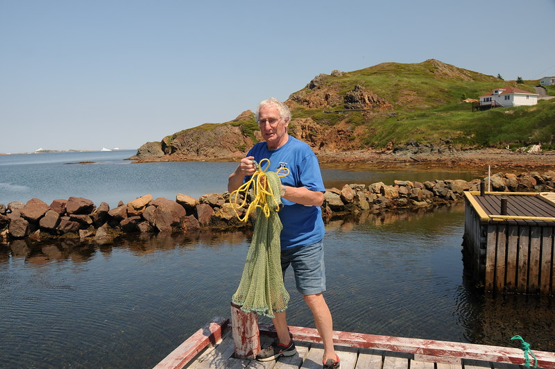 Mel demonstrates how he tossed a fish net during capelin rolling in 2001.<br /> <br /> Check out the picture Mel and Sharon are holding in the previous photograph.