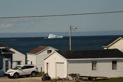 "On the way through St. Barbe, we stopped for a photo of this iceberg passing through the Strait of Belle Isle, with Labrador in the background.  During the iceberg season, some of the white giants make a turn into the Strait of Belle Isle, in the western waters off Newfoundland, instead of the usual route down the east side known as ""Iceberg Alley."""