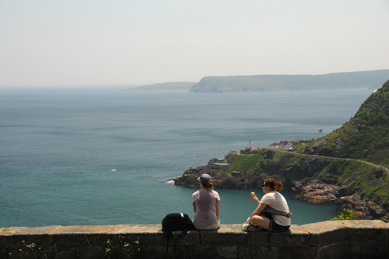 It certainly is a more tranquil place down here.<br /> These ladies are sitting above the St. John's harbour entrance, enjoying the view east out into the Atlantic Ocean.<br /> Fort Amherst is in the background.