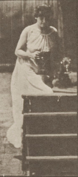 Semi-nude woman turning to ascend stairs, with a pitcher and goblet in hands