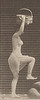 Semi-nude woman stepping on and over a rock holding a basket on her head with the right hand raised