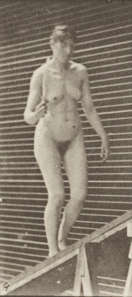 Nude woman ascending an incline and flirting a fan