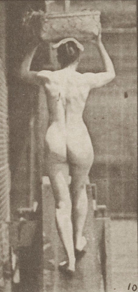 Nude woman ascending an incline with a 20-lb. basket on head