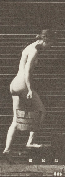 Nude woman turning and ascending stairs with a bucket of water