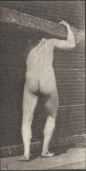 Nude man lifting a log on shoulder