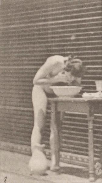 Nude woman washing face