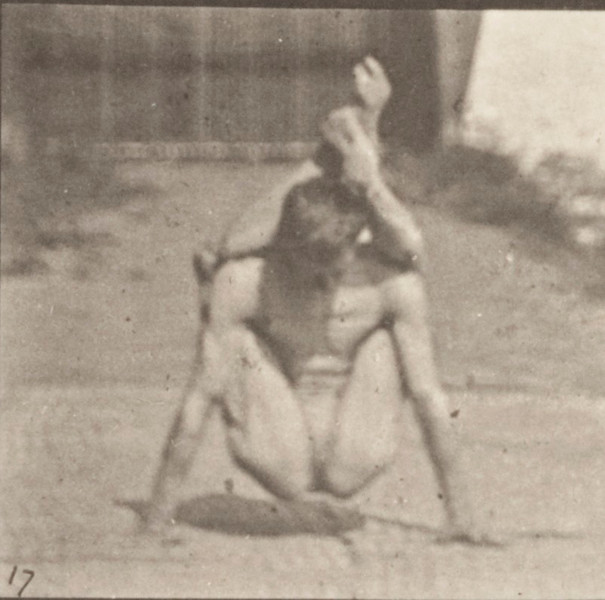 Man in pelvis cloth performing contortions on the ground