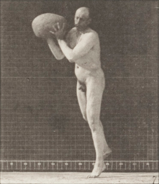 Nude man heaving a 75-lb. rock