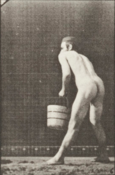 Nude man lifting a bucket of water to empty it