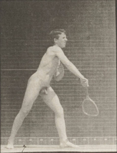 Nude man playing lawn tennis, serving