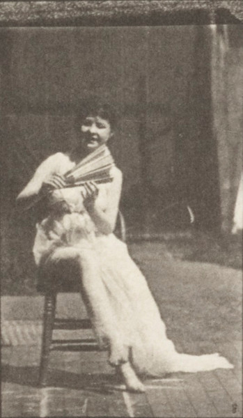 Draped woman placing a chair, sitting and flirting a fan