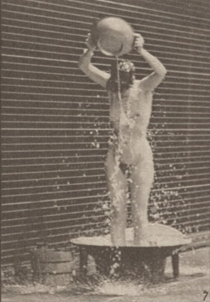 Nude woman pouring water over head