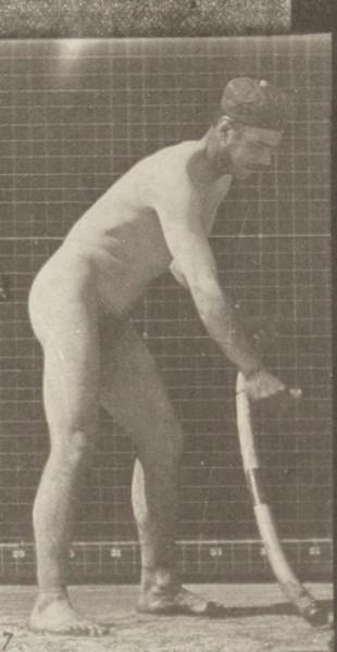 Nude farmer mowing grass