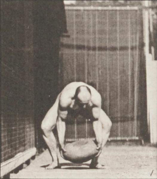 Nude man heaving a 75-lb. rock