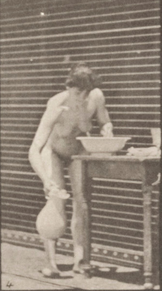 Nude woman washing face