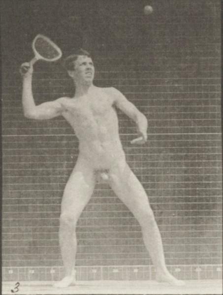 Nude man playing lawn tennis, serving