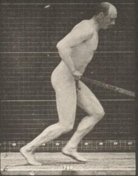 Nude man pushing a garden roller