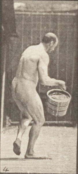 Nude man emptying a bucket of water