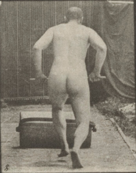 Nude man pushing a garden roller