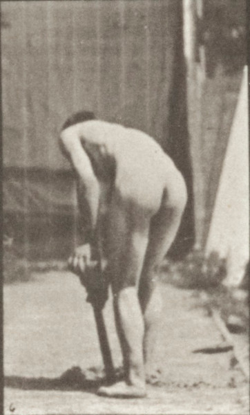 Nude farmer using a spade