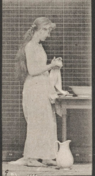 Woman brushing hair and washing face