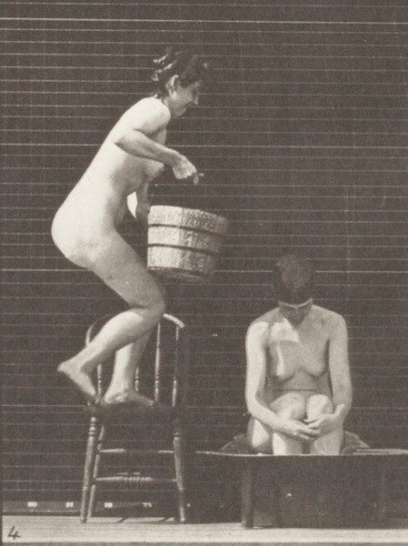 Nude woman pouring a bucket of water over another nude woman