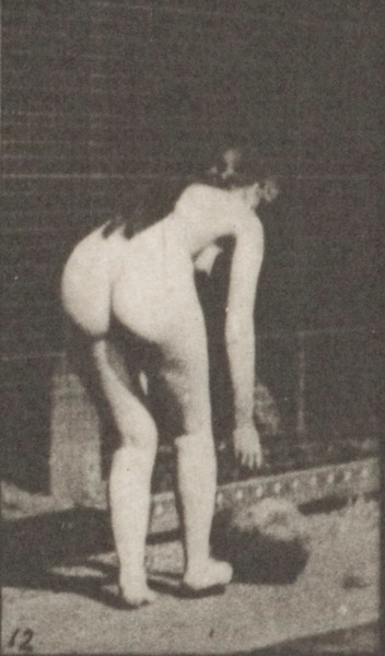 Nude woman stooping and rolling a stone on the ground