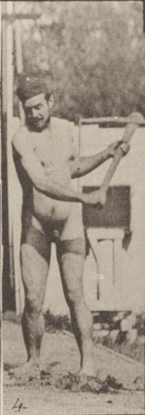 Nude farmer using a pick