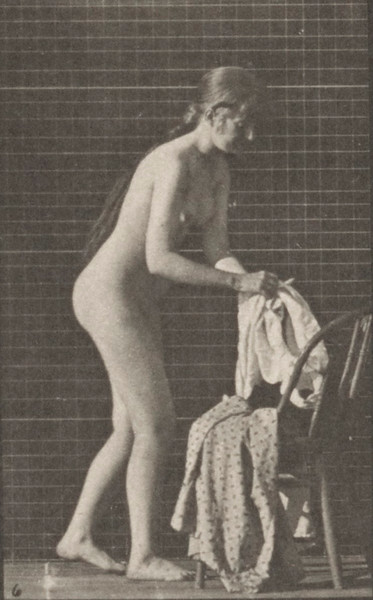 Nude woman standing and putting on clothes