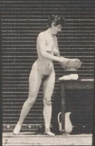 Nude woman emptying a basin of water