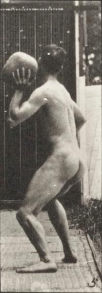 Nude man heaving a 20-lb. rock