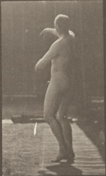 Nude man picking up a ball and throwing it
