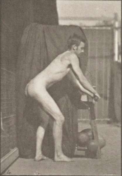 Nude man turning a crank handle