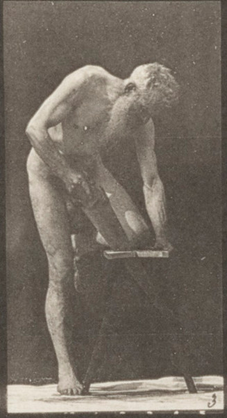 Nude man sawing a board