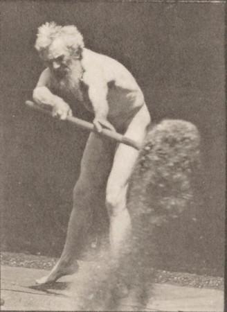 Nude man using a shovel