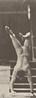 Male acrobat wearing pelvis cloth descending stairs on hands
