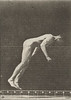 Nude man performing a running somersault