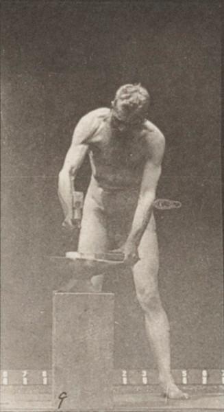 Nude man hammering at an anvil
