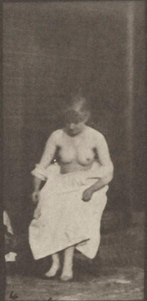 Nude woman sitting and disrobing