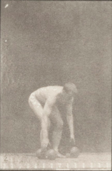 Nude man picking up and lifting dumbbells