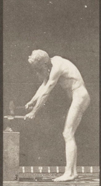 Nude man hammering at an anvil