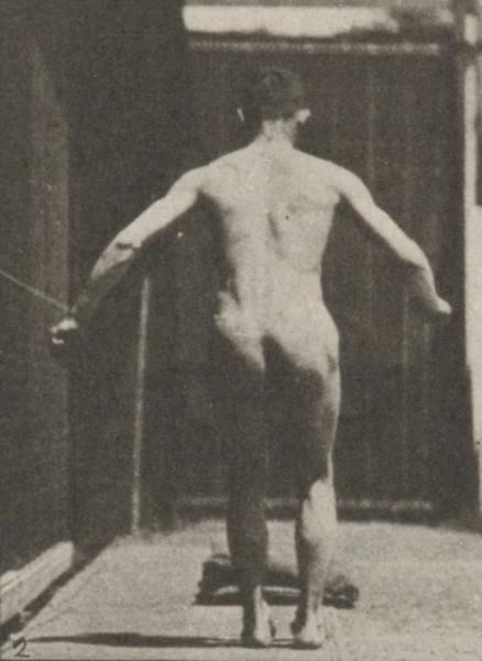 Nude man performing a running somersault