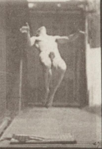 Nude man performing back somersault