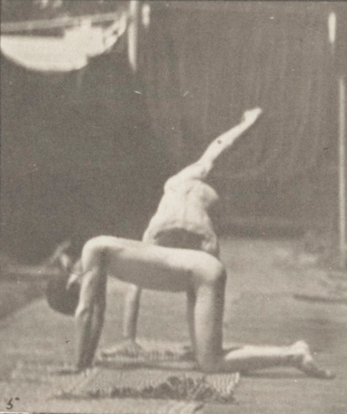 Nude man doing a handspring over another nude man's back