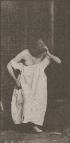 Nude woman sitting and disrobing