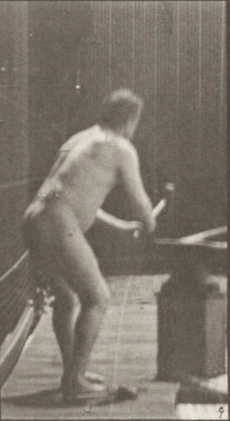 Nude blacksmith hammering on anvil with two hands
