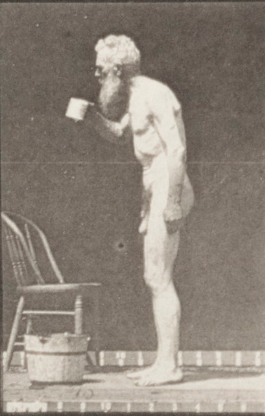 Nude man stooping for cup and drinking