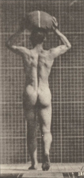 Nude man walking and carrying a 75 lb. stone on head, hands raised